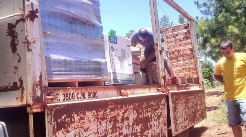 Militantes del PAyS con los materiales para construir el baño de la Abuela María
